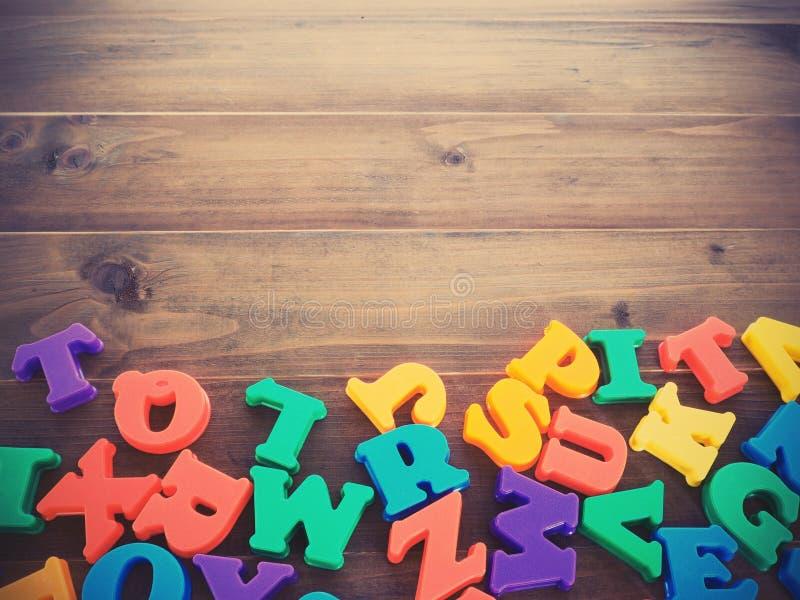 Färgrika plast- alfabet på trätabellbakgrund, tappning f royaltyfria bilder
