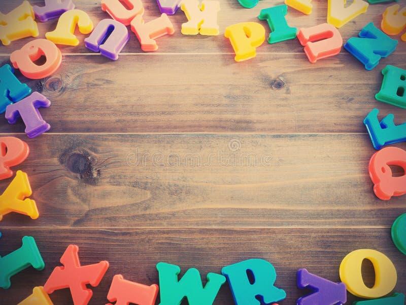 Färgrika plast- alfabet på trätabellbakgrund, tappning f royaltyfria foton