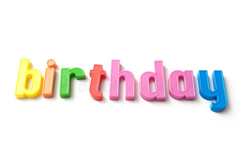 färgrika plast- bokstäver på vit bakgrund - födelsedag arkivfoto