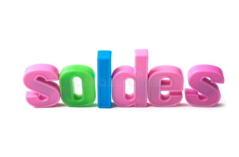 färgrika plast- bokstäver på vit bakgrund - Soldes i franskt - traduction i engelska försäljningar royaltyfri foto