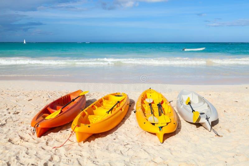 Färgrika plast- kajaker lägger på den tomma sandiga stranden royaltyfri foto