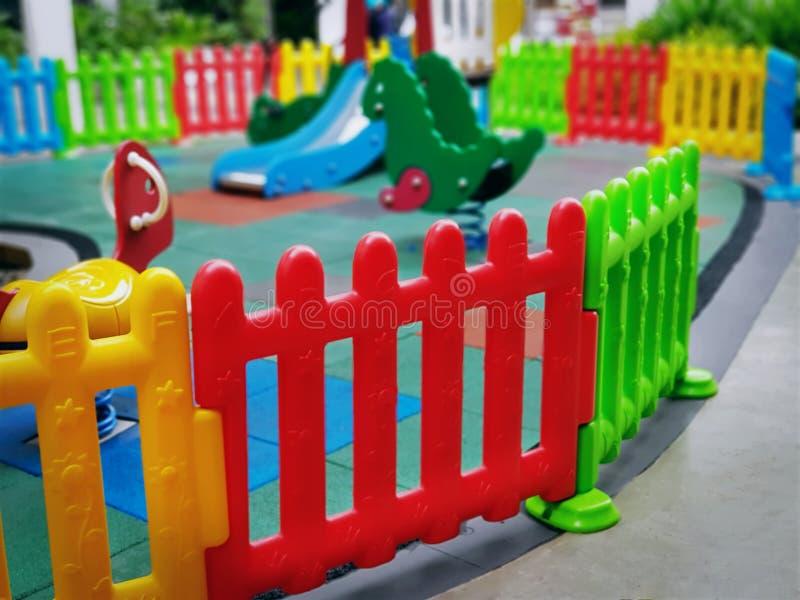 Färgrika plast- staketArounds Kids lekplats med den selektiva fokusen fotografering för bildbyråer