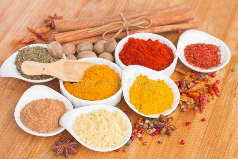 Färgrika plattor av kryddor på tabellen arkivbilder