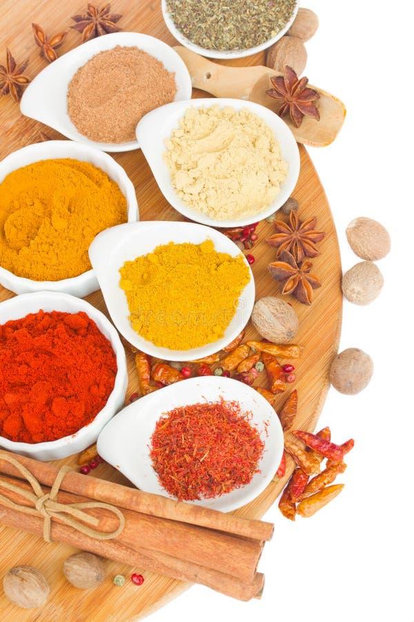 Färgrika plattor av kryddor på träbräde royaltyfri fotografi