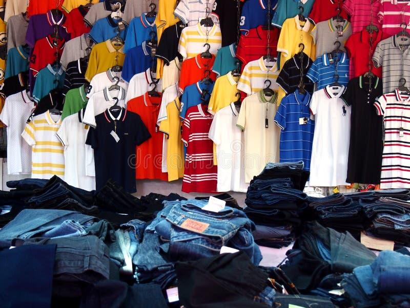 Färgrika poloskjortor och högar av grov bomullstvilljeans på skärm på ett kläderlager arkivfoto