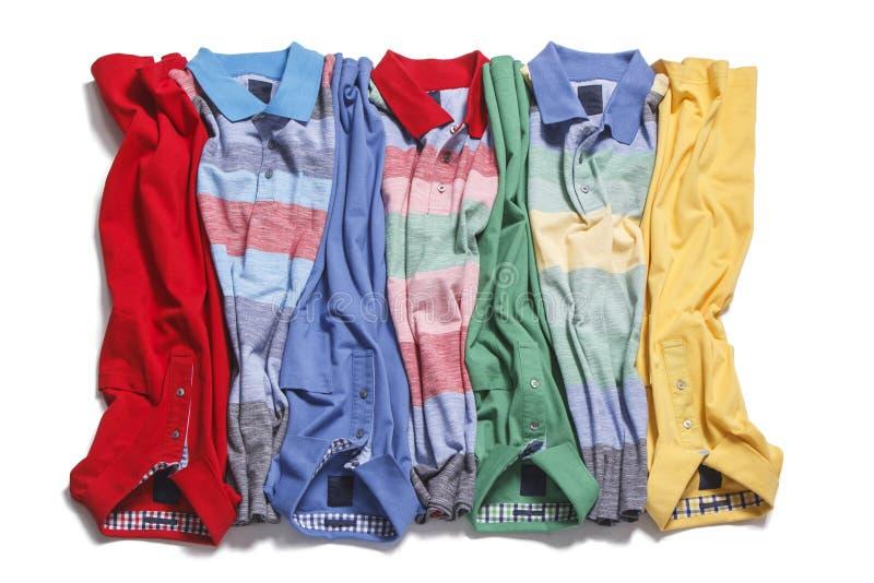 Färgrika poloskjortor som lägger på vit bakgrund arkivbild