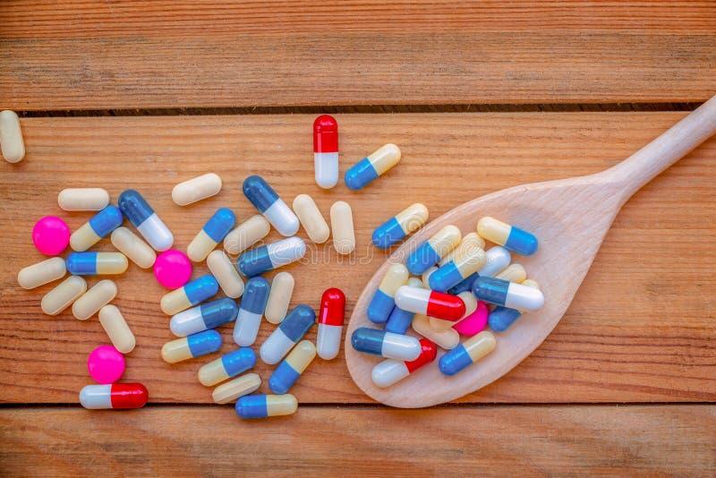 Färgrika preventivpillerar och läkarbehandling i en trämatlagningsked, på wood plankabakgrund, vård- läkarbehandlingbegrepp royaltyfria foton
