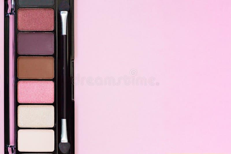 Färgrika produkter för makeup för palett för ögonskugga på pastellfärgad rosa bakgrund med kopieringsutrymme royaltyfri foto