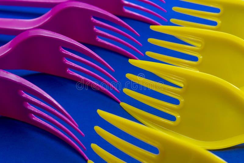 Färgrika purpurfärgade och gula plast- gafflar på blått arkivbild
