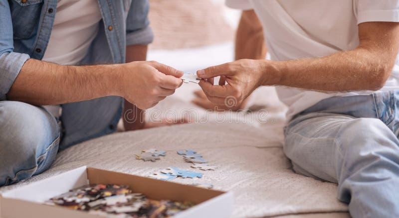 Färgrika pusselstycken i händer av två män arkivbild