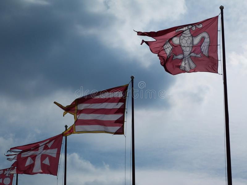 färgrika röda och vita flaggor i abstrakt sikt med cloudscape arkivbild