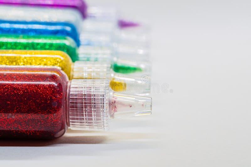 Färgrika rör som fylls med, blänker lim fotografering för bildbyråer