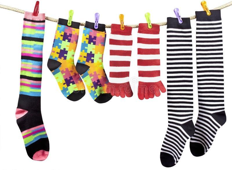 Färgrika roliga sockor som torkar på klädstrecket fotografering för bildbyråer
