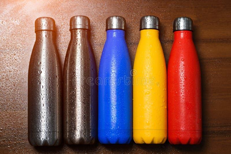 Färgrika rostfria thermo flaskor, på en trätabell som besprutas med vatten Den Matte röd flaskan, blått, guling och platina färga royaltyfri fotografi