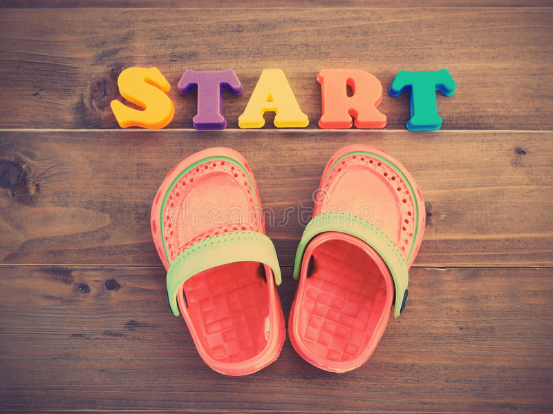 Färgrika rubber sandaler för barn` s och färgrika alfabet STARTAR royaltyfri foto