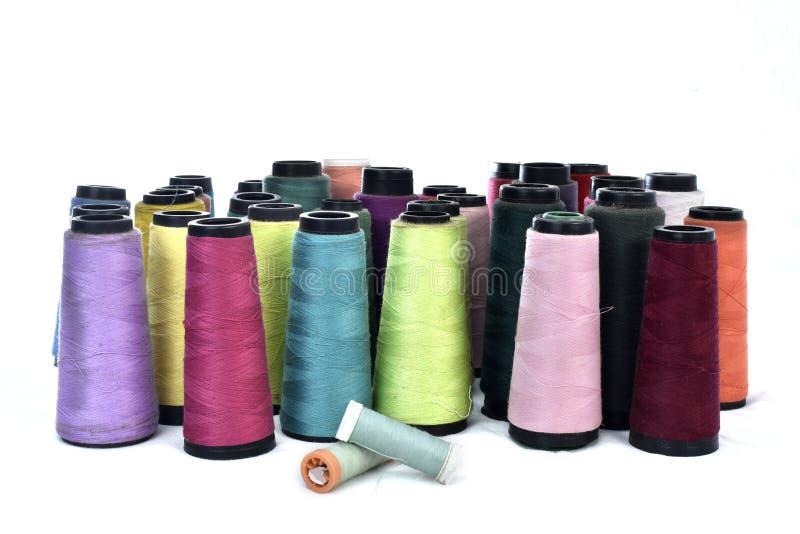 Färgrika rullar för sy tråd på vit bakgrund arkivfoton