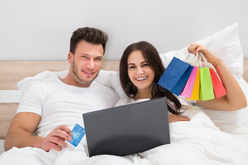 Färgrika shoppingpåsar med par som ligger på säng arkivbild
