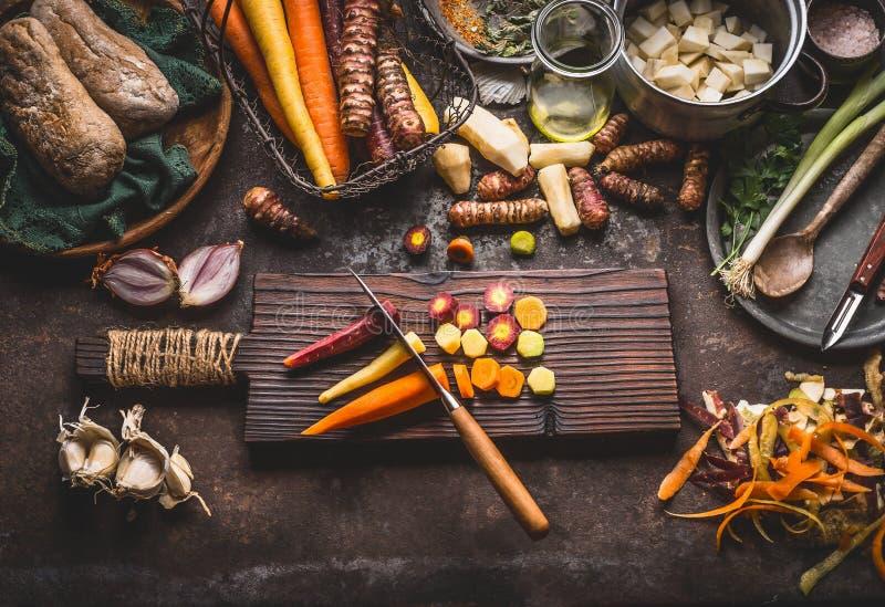 Färgrika skivade morötter med kniven på träskärbräda på lantlig köksbordbakgrund med rotfruktingredienser för fotografering för bildbyråer