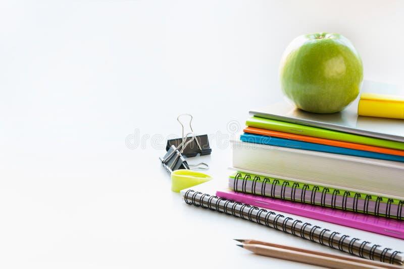 Färgrika skolatillförsel, bok, äpple på vit close upp tillbaka skola till fotografering för bildbyråer