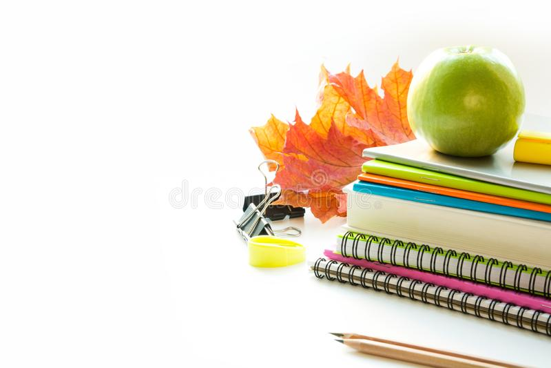 Färgrika skolatillförsel, bok, äpple på vit close upp tillbaka skola till arkivfoton