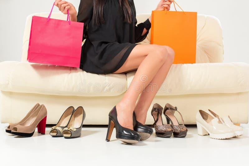 Färgrika skor och påsar med kvinnasammanträde på soffan royaltyfri bild