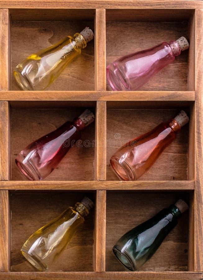 Färgrika små flaskor i en träask royaltyfri bild