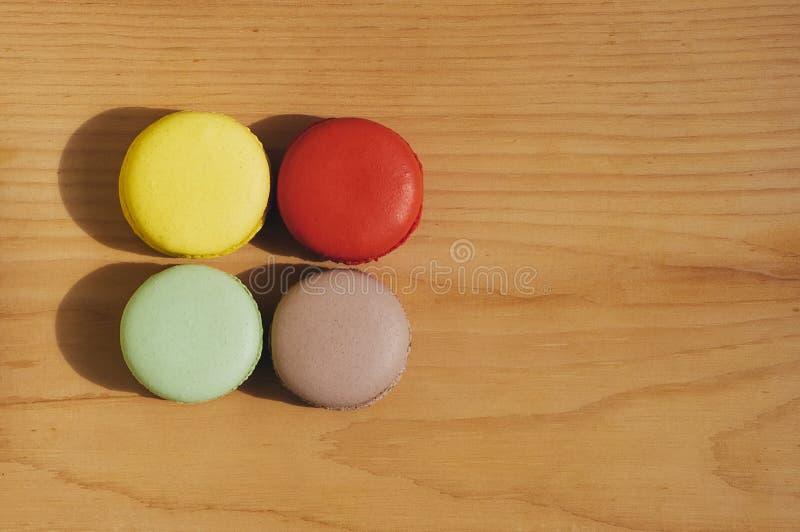 Färgrika smakliga franska macarons som isoleras på trätextur arkivbild