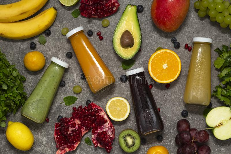 Färgrika smoothies i flaskor med nya tropiska frukt och grönsaker på konkret bakgrund, bästa sikt Lekmanna- lägenhet royaltyfria foton
