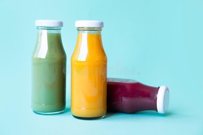Färgrika smoothies i glasflaskor som isoleras på blå bakgrund, bästa sikt arkivfoton