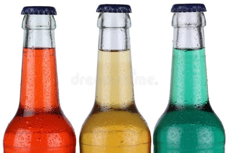 Färgrika sodavattendrinkar i isolerade flaskor royaltyfri fotografi