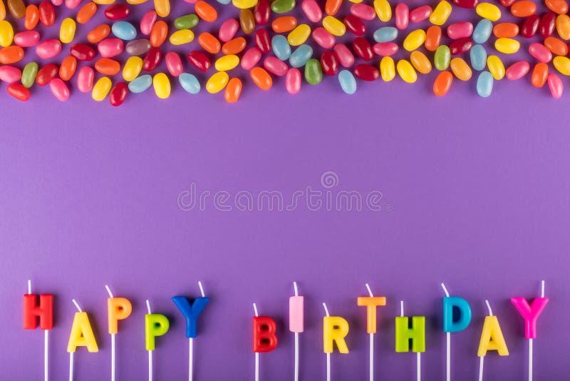 Färgrika stearinljus för lycklig födelsedag för kaka- och gelébönor arkivfoto