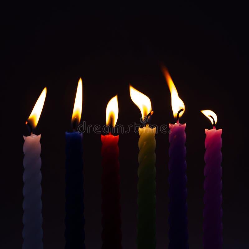 Färgrika stearinljus på svart bakgrund Blå röd grön violett rosa färgstearinljus med den verkliga flamman mjuk fokus, grunt djup  royaltyfri foto
