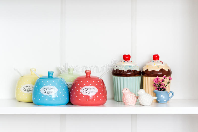 Färgrika Sugar Bowls i en vit hylla arkivfoton