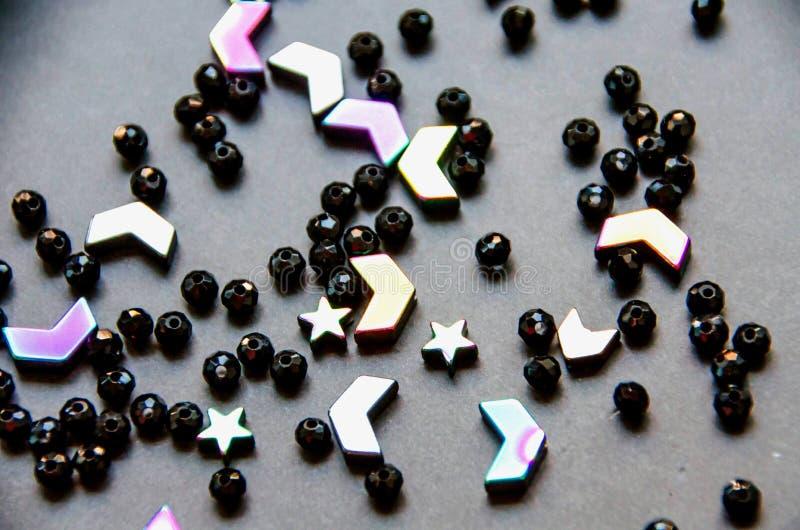 Färgrika svarta pärlor och stenar som isoleras på grå bakgrund arkivbilder