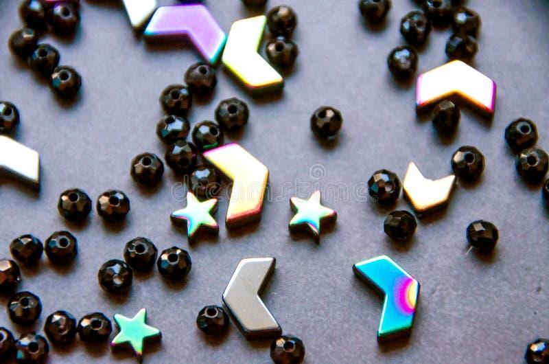Färgrika svarta pärlor och stenar som isoleras på grå bakgrund arkivfoton