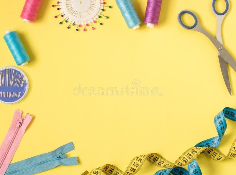 Färgrika sy tillförsel och tillbehör för handarbete på en gul bakgrund arkivbilder