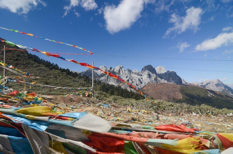 F?rgrika tibetana flaggor med bl? himmel p? siktspunkt l?ngs v?gen till den Yading naturreserven royaltyfri fotografi
