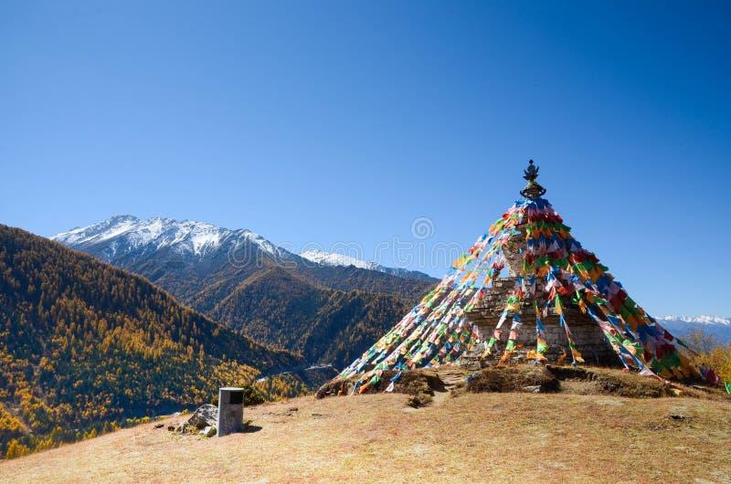 Färgrika tibetana flaggor och snöberg på Siguniang sceniskt område i Kina royaltyfri bild