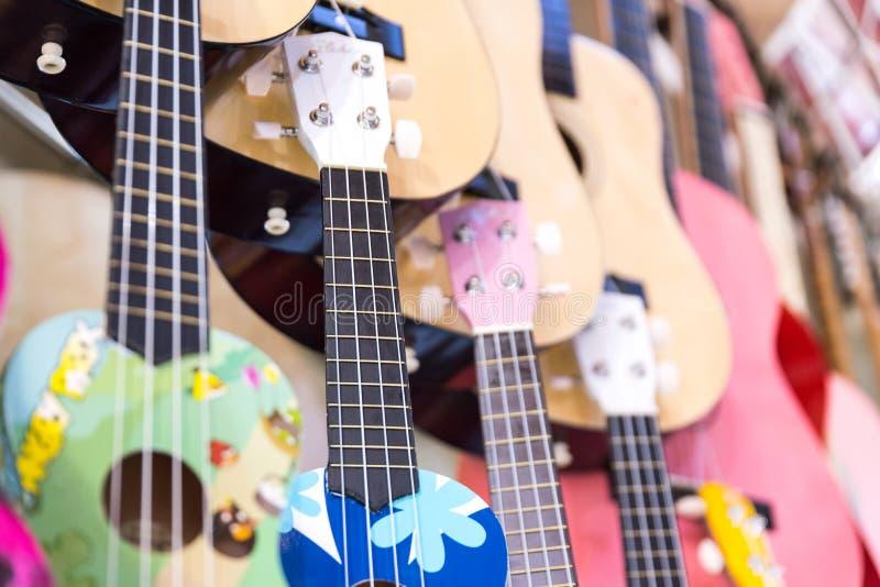 färgrika trägitarrer som hänger på väggen av lagervisningslokalen royaltyfri fotografi