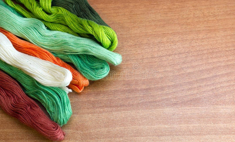Färgrika trådar på en träbakgrund arkivbilder