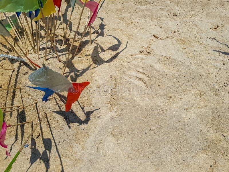 Färgrika triangelpappersflaggor klibbar på sandbakgrund med copyspace för framställning av den traditionella sandpagoden på den S royaltyfria bilder
