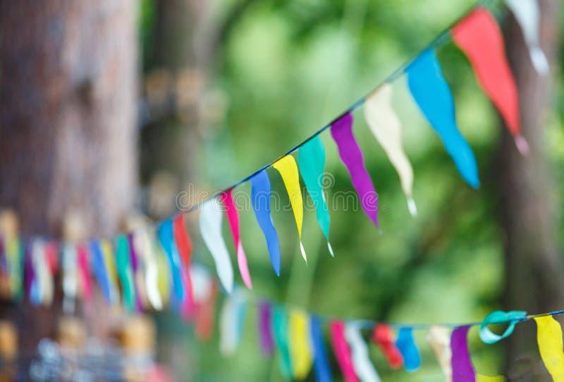 Färgrika trianglar i sommaren parkerar Födelsedag partidekor royaltyfri foto