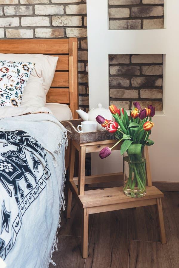 Färgrika tulpan i vas är i modernt sovrum arkivfoto