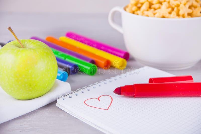 Färgrika tuschpennor, anteckningsbok med scetch, bunke av stjärnan formade sädesslag och äpplet på den gråa bakgrunden arkivfoton