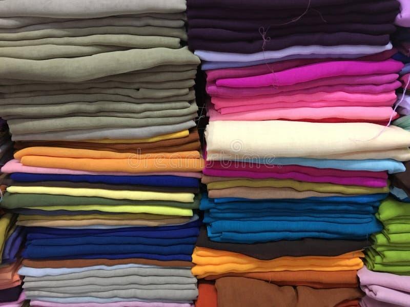 Färgrika tygbomullsrullar uppställda för modesamlingen, begrepp: Bekläda produktbransch för shoppa i marknaden, royaltyfria bilder