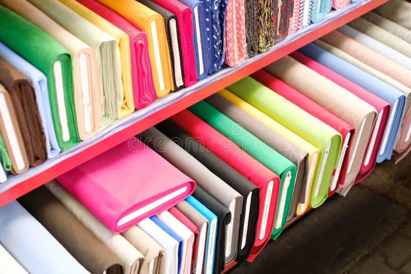 Färgrika tygrullar på textilmarknad - arkivfoto