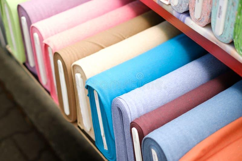 Färgrika tygrullar på textilmarknad - arkivfoton