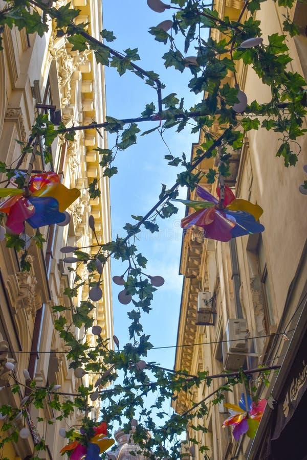 Färgrika väderkvarn- och blommagarneringar mot den blåa himlen på en smal gata med gamla byggnader i Bucharest, Rumänien arkivbilder