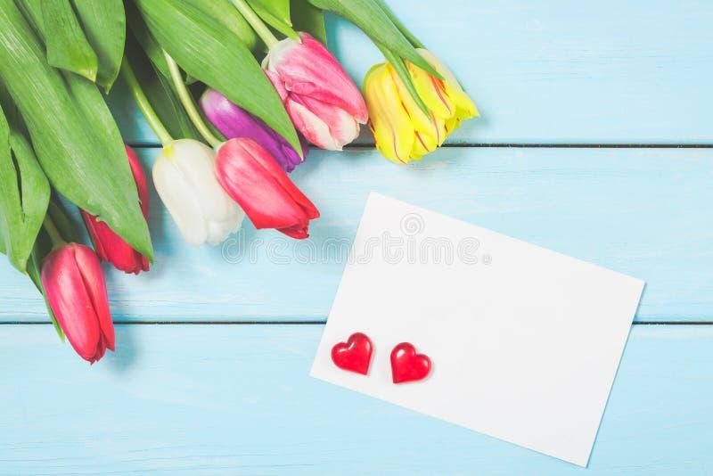 Färgrika vårtulpanblommor med tom photoframe och hjärtor på ljus - blå träbakgrund som hälsningkort med fritt utrymme M royaltyfri fotografi
