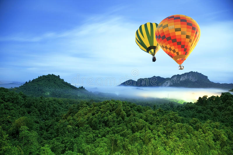Färgrika varmluftsballonger som flyger över berget royaltyfri fotografi